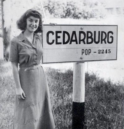 Woman standing next to Cedarburg town sign with population of 2,240.
