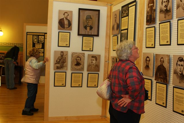 Woman looking at old presented Civil War photos.