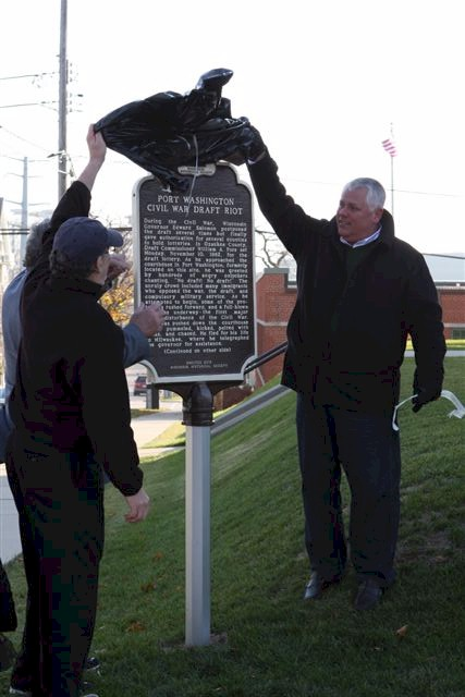 Three people revealing historical marker.