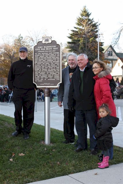 Group of people standing next to historical marker.