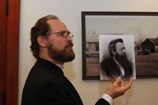 Man holding historical picture of another man comparing profiles.