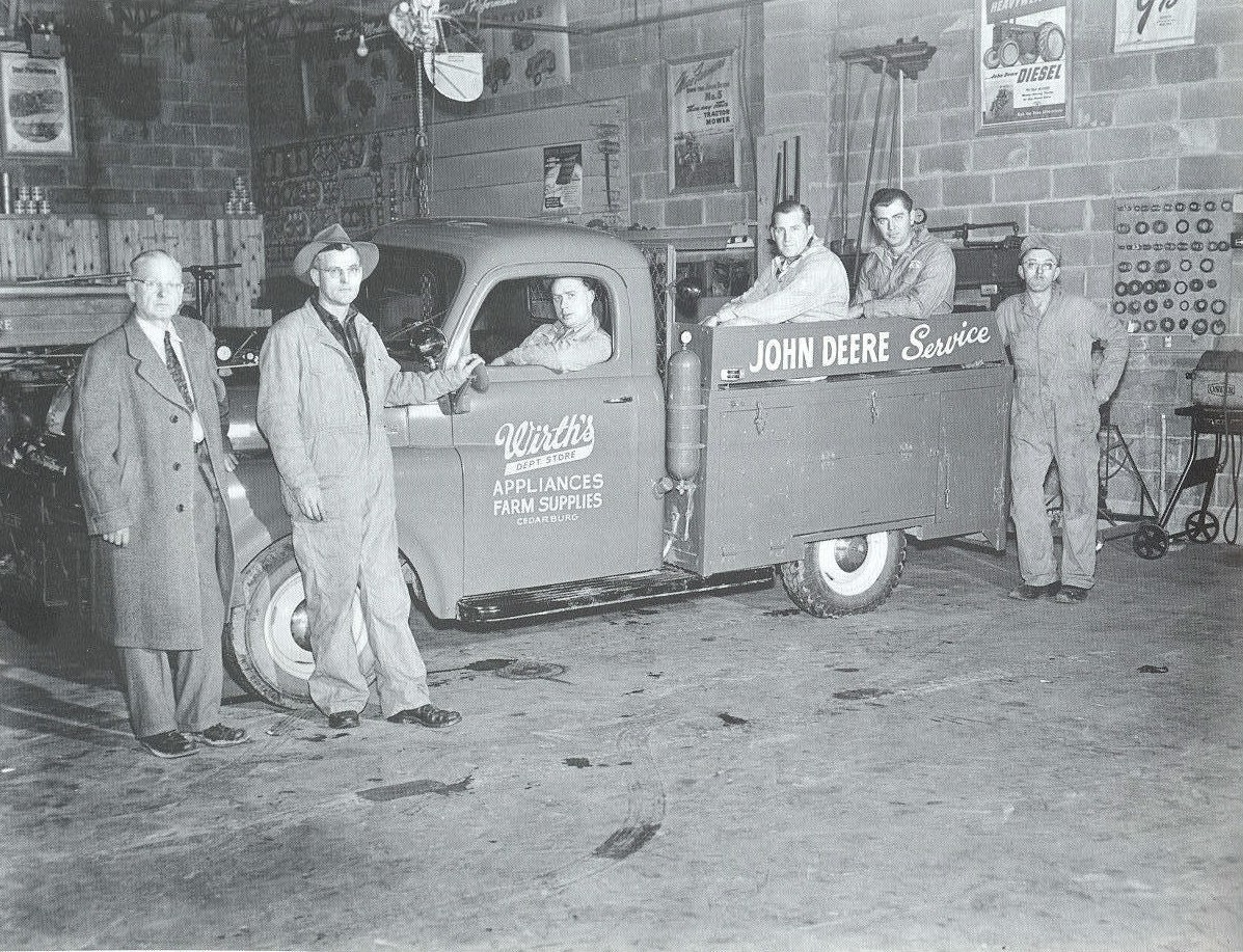 Service department men standing with John Deere service Wirth Department Store pickup.